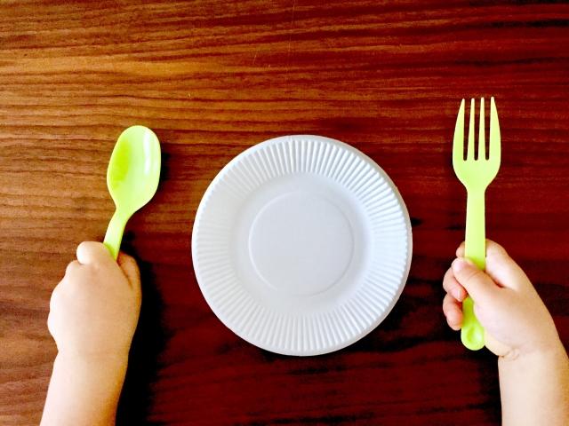 子供の手とフォークとスプーン